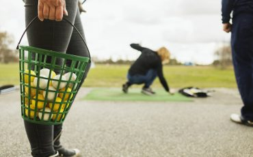 Low section of woman holding basket with balls at golf course